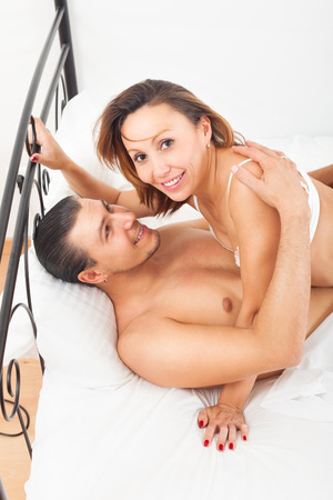 Adult couple having sex on bed in bedroom interior at home photo