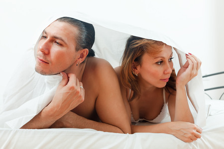 Unhappy man and woman having  problem under sheet photo