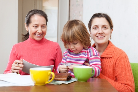 Mature woman and adult daughter with child is calculates the family budget at  home Stock Photo - 23369629
