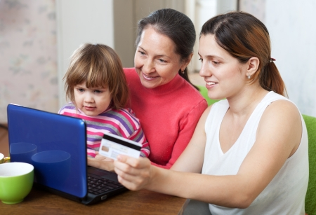 Family of three generations doing shopping in internet with credit card at home photo