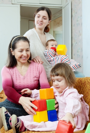 Portrait of happy mature woman and her adult daughter plays with children at home interior photo