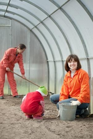 Mujeres felices con el niño trabaja en invernadero en primavera Foto de archivo - 23369842