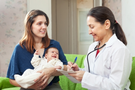 children's doctor: childrens doctor examining newborn baby on mothers arms. Focus of mother Stock Photo