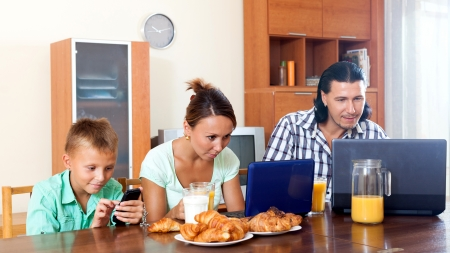 ordinary couple with teenager son using devices during breakfast at home photo