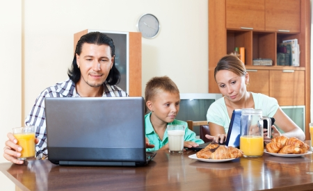 parents and teen bay having breakfast in a house interior 