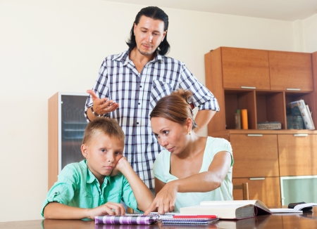 berate: underachiever teenager schoolboy and parents together doing homework in home