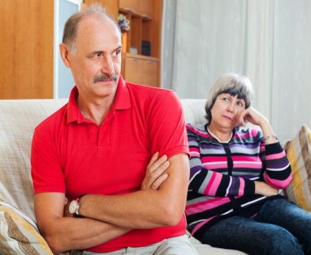 Senior married couple having quarrel at home photo