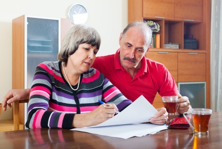 serious mature couple fills in questionnaire together at home interior photo