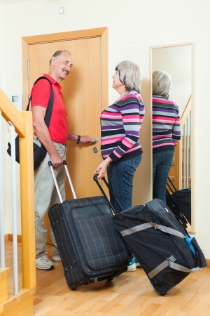 Mature couple with suitcases near door at home photo