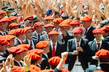 berets: PAMPLONA, SPAIN - JULY 6: Start of San Fermin festival in July 6, 2013 in Pamplona, Spain. Municipal Orchestra playing  at ayuntamiento square as a sign of beginning of  festival