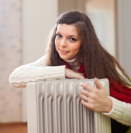 Portrait of long-haired woman near oil heater at her home