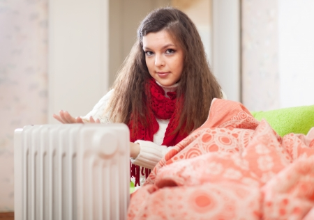 Woman warms hands near radiator at home