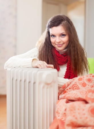 Smiling long-haired woman near oil heater at her home