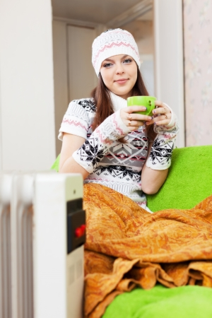 heat register:  girl relaxing with cup of tea at home  in winter Stock Photo