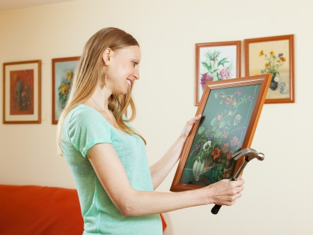 Positive blonde girl hanging art pictures on wall at house photo