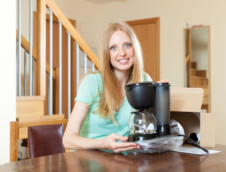 Smiling young blond with new electric coffee maker at home behind the table photo