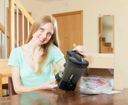 Happy woman reading  warranty card for new coffee machine  at home interior photo