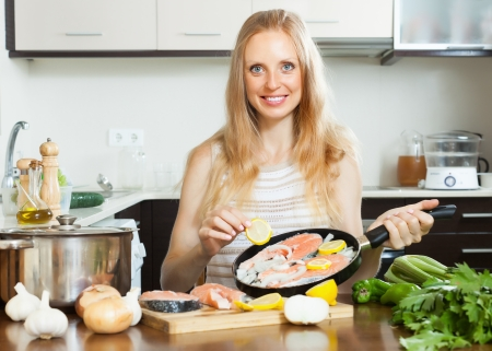 Smiling woman cooking salmon  with lemon on griddle  photo