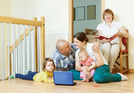 loving married couple with children and  grandmother in home interior together photo