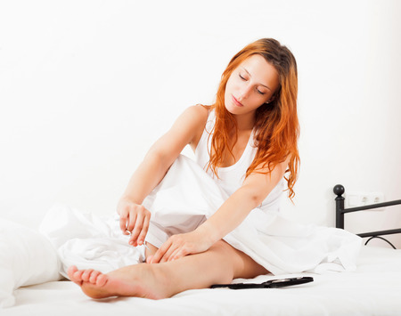 Beautiful red-haired girl cares for toenails with scissors in bed  at home Stock Photo - 23515750