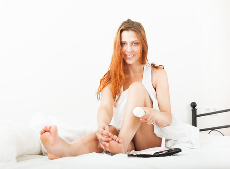 Smiling young woman uses cosmetic cream in bed at home Stock Photo - 23515755