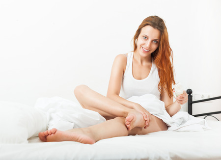 Smiling pretty young woman putting cream on legs in bad Stock Photo - 23539806