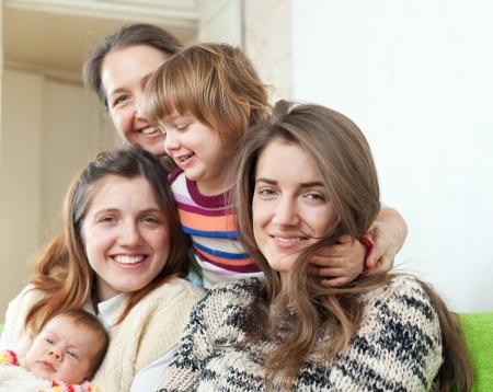 three generations of women: Happy women of three generations sits on sofa in livingroom  Stock Photo