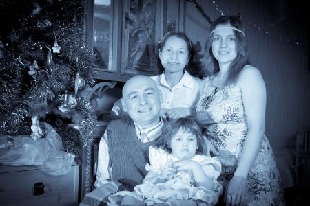Retro photo of happy family near Christmas tree at home photo