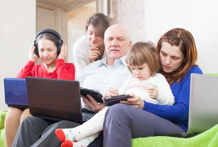 Family uses few various portable computers at home   photo