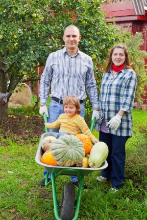 Happy parents and child with  harvested pumpkins in garden photo
