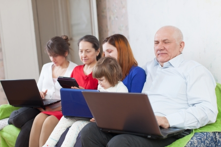 Happy multigenerations family on sofa in livingroom  with electronic devices at home Stock Photo - 23539976