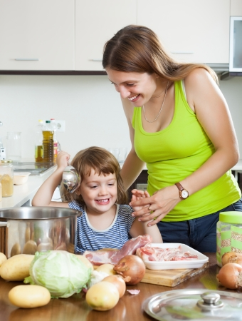 Smiling woman with little girl cooking together at home kitchen photo