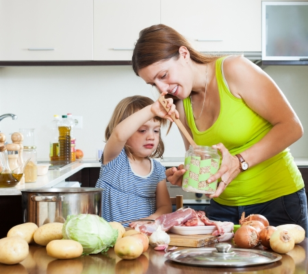 Happy mother with baby cooking with meat and vegetables photo
