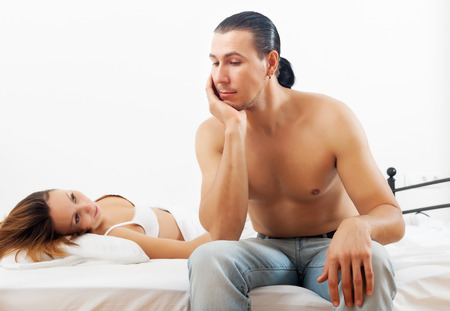 Unhappy man has problem near wife in bed photo