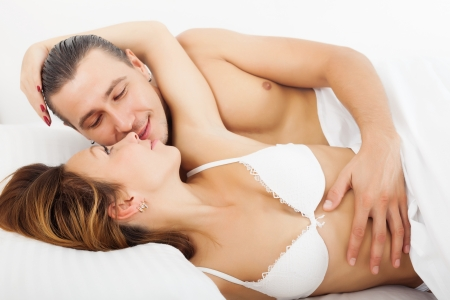 Loving man and woman awaking together on bed photo