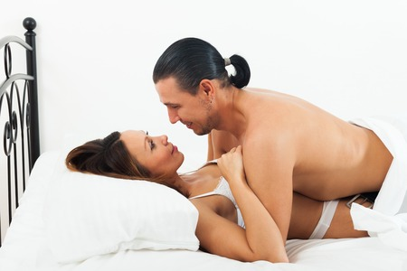 Couple having sex on bed in home interior photo