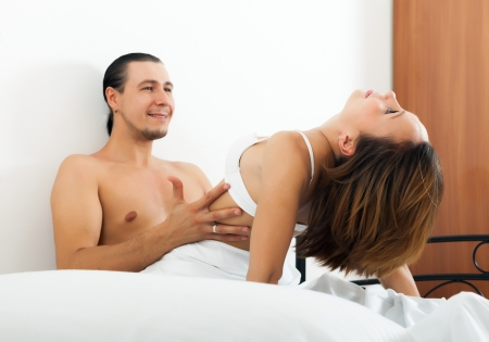 Handsome man having sex with woman in bed. Focus on girl photo