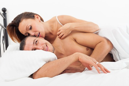 Middle-aged lovers kissing and playing in bed at home photo