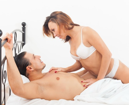 Middle-aged man with wife kissing and playing in bed at home photo