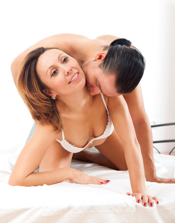 adult sex: Happy adult couple having sex on bed in bedroom Stock Photo