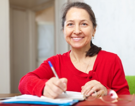 Smiling mature woman fills in documents at home Stock Photo - 23718580