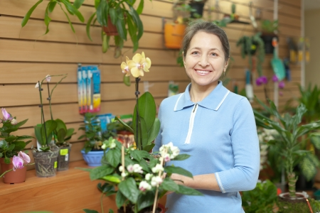 Happy mature woman with Phalaenopsis in pot at flower store photo