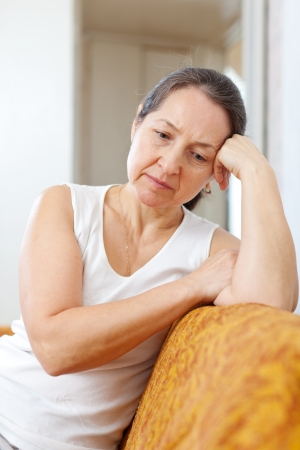 unhappy people: unhappy mature woman on sofa at  home Stock Photo