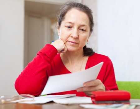 utility payments: serious mature woman reads payment bills at home Stock Photo