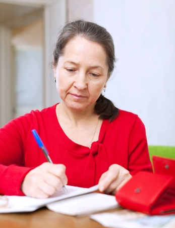serious mature woman fills utility bills at home Stock Photo - 23718502
