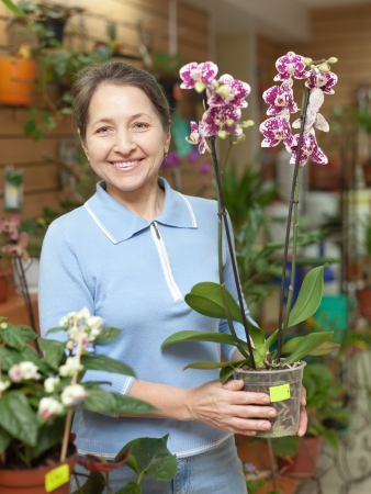 Happy mature woman with Phalaenopsis orchid at flower shop photo