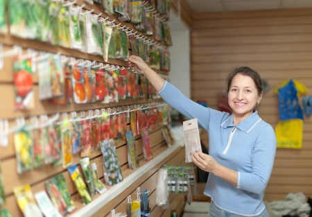 Female saleswoman with vegetable seeds at store photo