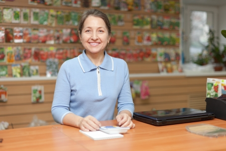 friendly mature woman selling seeds in store for gardeners photo