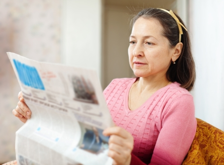 serious mature woman reading fresh newspaper  at home Stock Photo