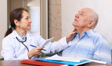 mature doctor touching  neck of  senior man in clinic  Stock Photo